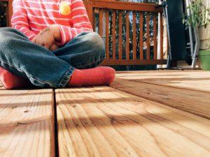 Child sitting on wooden deck