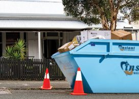 Skip bin and witches hats on the road in front of a house