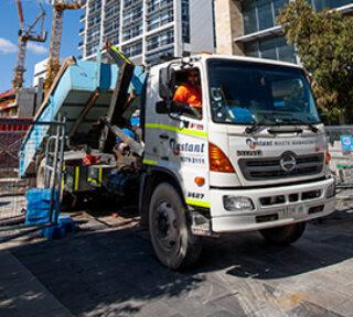 Instant waste truck tipping a skip bin
