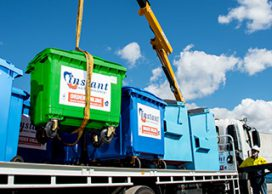 Numerous large recycling bins on the back of a truck in different colours
