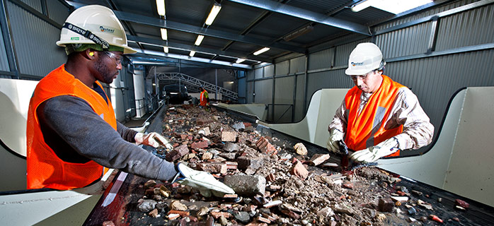 Workers going through recycling at picking station